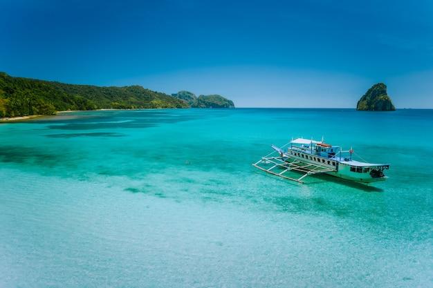 Barco atracado em lagoa azul turquesa rasa e calma