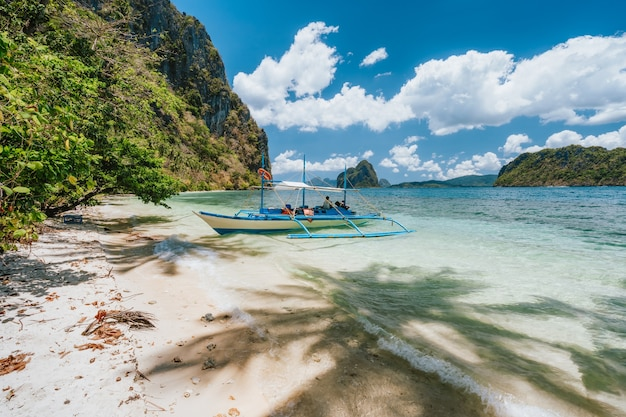 Barco atracado na solidão tropical isolada praia arenosa. el nido, palawan, filipinas.