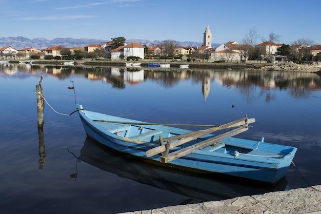 Barco azul amarrado ao longo do cais em uma vila