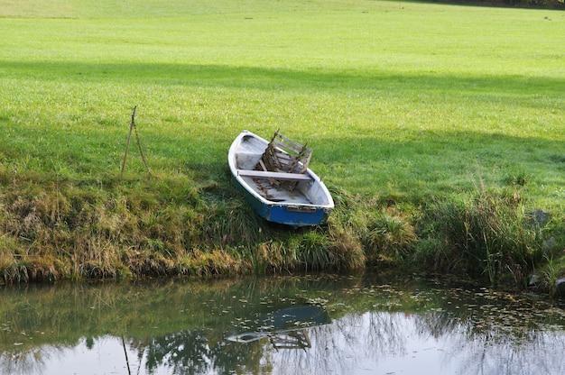 Barco azul velho perto de um lago em uma floresta durante o dia