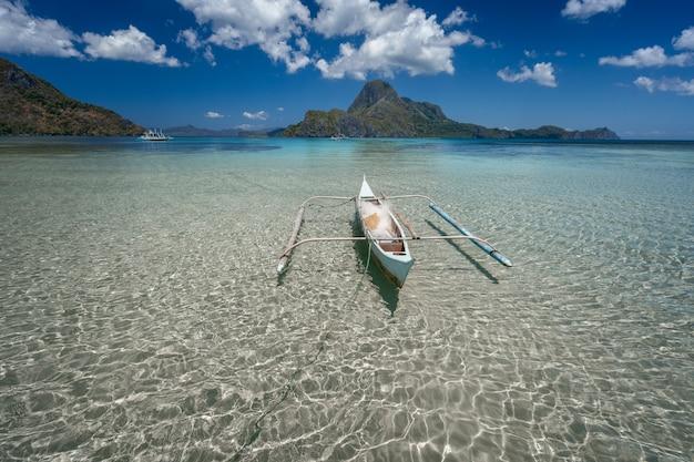 Barco banca em águas rasas cristalinas com uma ilha tropical no fundo. el nido, palawan, filipinas.