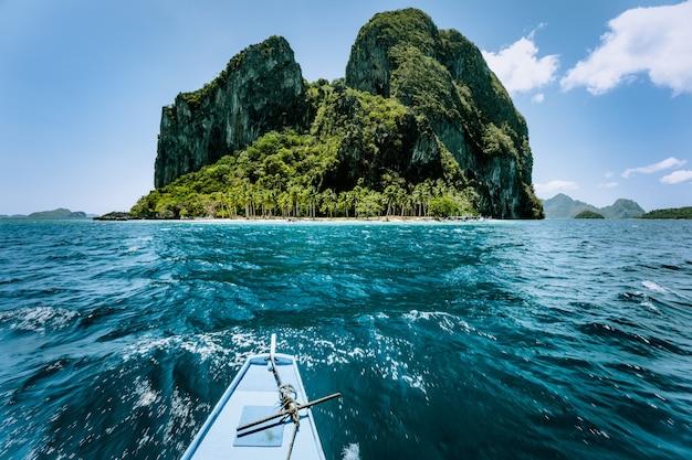 Barco banca local aproximando-se da incrível viagem de excursão à ilha tropical para o famoso arquipélago protegido bacuit el nido, atrações turísticas locais em palawan nas filipinas. Foto Premium