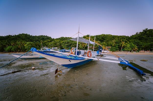 Barco banca na praia durante a maré baixa, no entardecer. el nido, palawan, filipinas