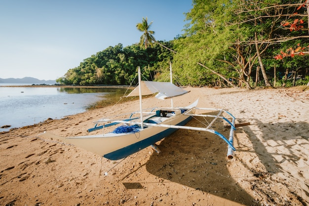 Barco bangka na praia remota com luz dourada do sol. baía de el nido. filipinas.