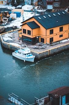 Barco branco na doca perto de casas durante o dia