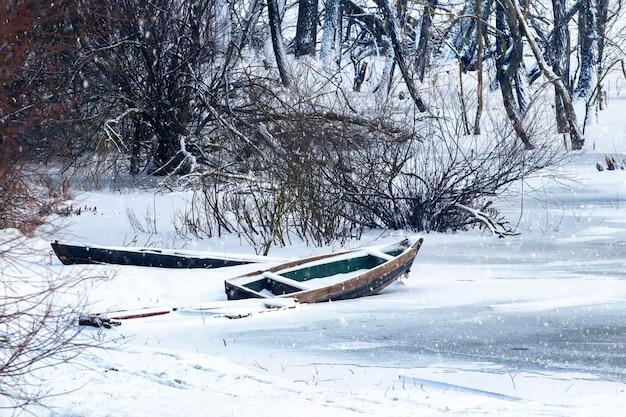 Barco coberto de neve no rio no inverno durante uma nevasca. árvores cobertas de neve perto do rio com um barco