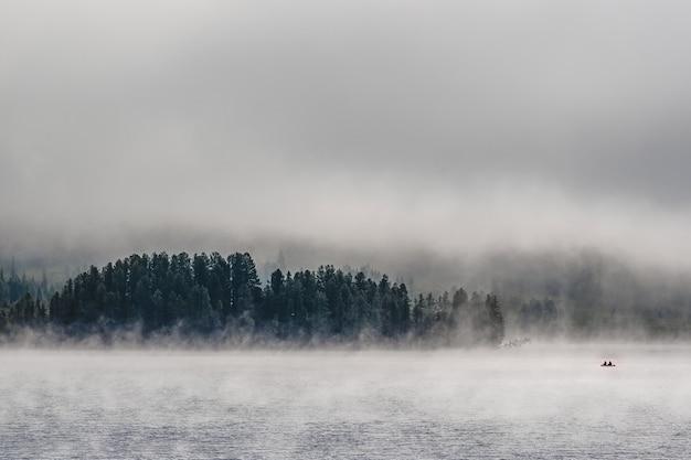Barco com pescadores em um lago de montanha coberto de névoa no distrito de ulagansky da república de altai, rússia