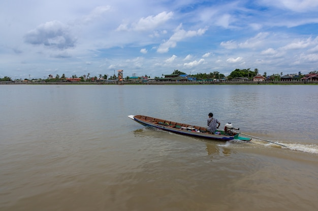 Barco da cauda longa no rio de chao phraya contra o céu nebuloso em banguecoque. tailândia.