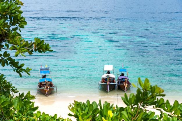 Barco da cauda longa que flutua no oceano no paraíso com água claro na ilha tailândia de phi phi.