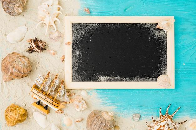 Barco de brinquedo e conchas entre areia perto de quadro-negro