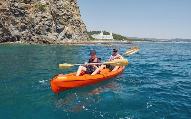 Barco de caiaque perto de falésias em um dia ensolarado. caiaque em uma baía tranquila. vistas incríveis. viagens, conceito de esportes. estilo de vida. uma família feliz.