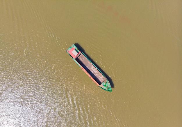 Barco de carga que flutua na região do delta do rio mekong, can tho, vietname do sul. diretamente acima da embarcação náutica de cima para baixo na água barrenta marrom.