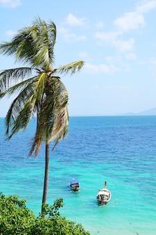 Barco de cauda longa e céu azul no paraíso com água cristalina bonita na ilha de phi phi