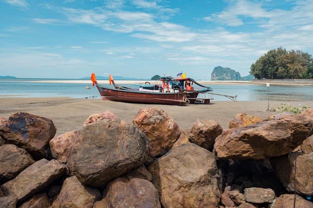 Barco de cauda longa e rochas na praia de areia tropical, mar de andaman, na tailândia