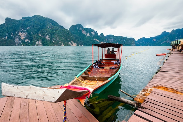 Barco de cauda longa flutuando no lago da ásia e homestay no entre as ilhas.