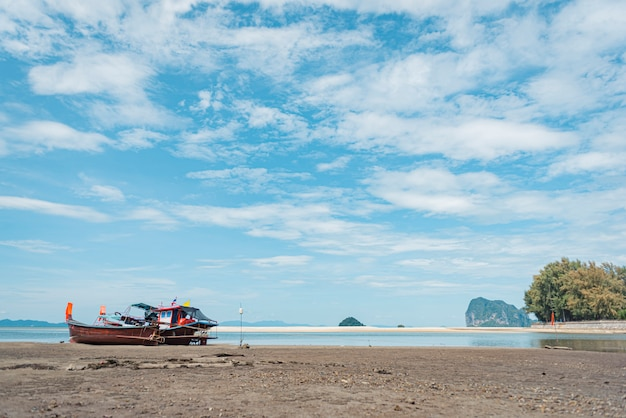 Barco de cauda longa na praia de areia tropical, mar de andaman, na tailândia
