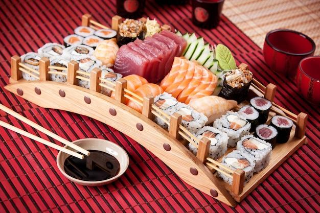 Barco de composição de sushi na superfície vermelha