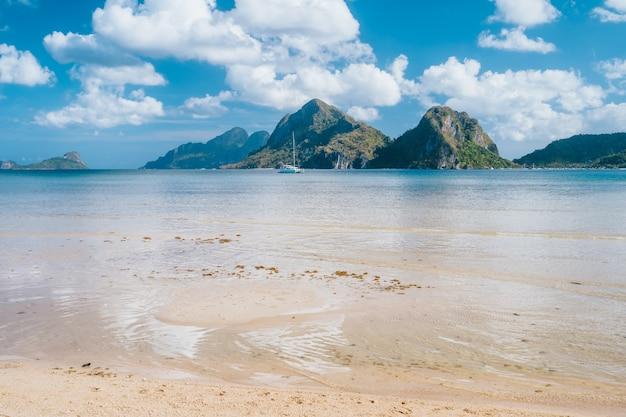 Barco de iate na lagoa do oceano com montanhas ao fundo. el nido, palawan, filipinas
