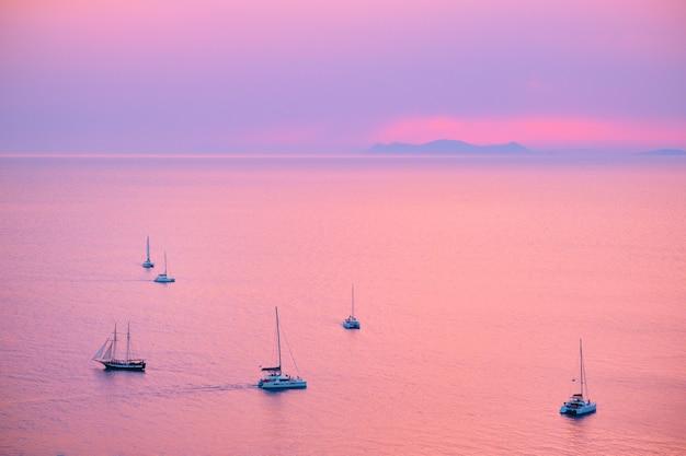 Barco de iates turísticos no mar egeu, perto da ilha de santorini, com turistas assistindo ao ponto de vista do pôr do sol em sant ...
