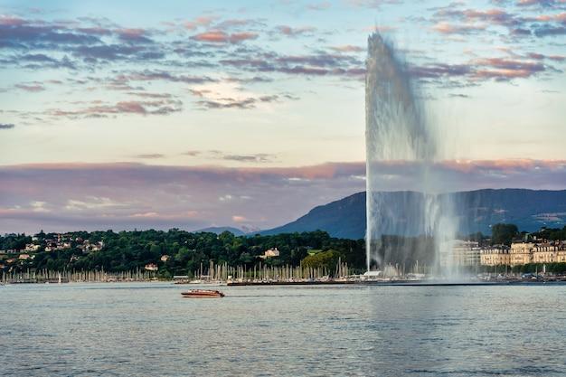 Barco de lazer passando pelo jato de água no lago leman, na cidade de genebra, na suíça