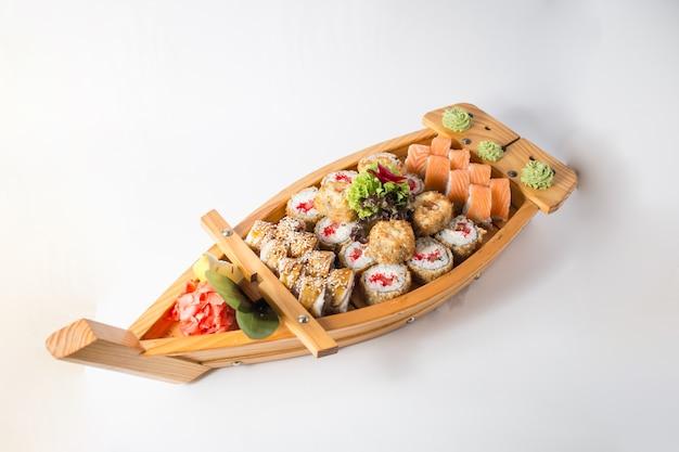 Barco de madeira com muito sushi com gengibre e wasabi.