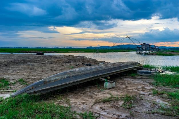 Barco de madeira e armadilha de rede de pesca no rio