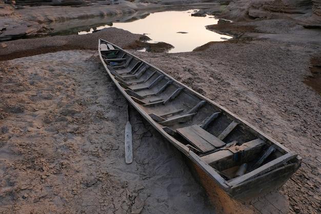 Barco de madeira em solo rachado, aquecimento global.
