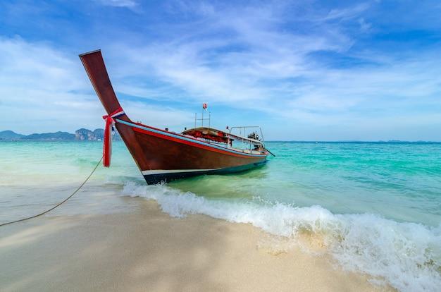 Barco de madeira estacionado no mar, praia branca em um céu azul claro, mar azul