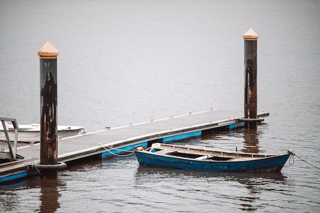 Barco de madeira gasto atracado no cais de madeira na água do mar em dia nublado