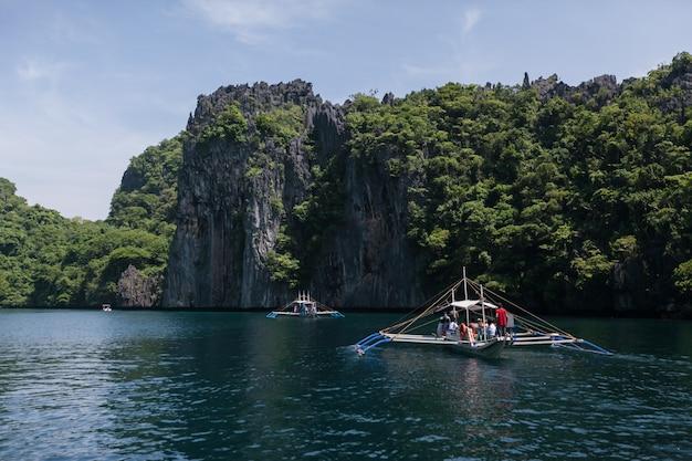 Barco de madeira na costa rochosa de calcário de lagoa azul. el nido, palawan, filipinas