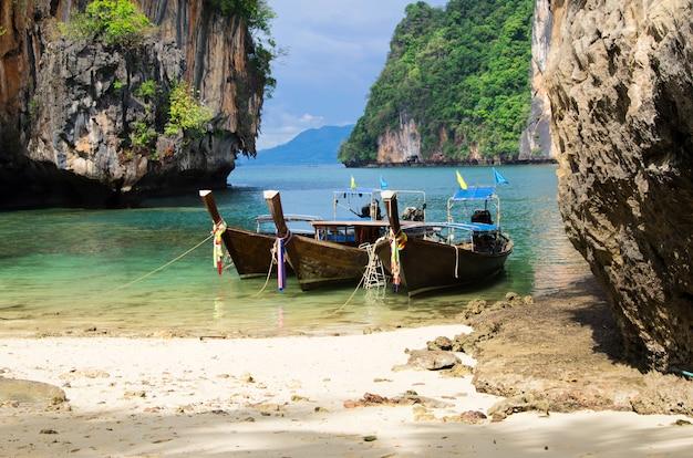 Barco de madeira na praia rochosa
