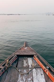 Barco de madeira navegando no rio ganges em varanasi, índia
