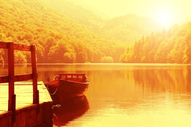 Barco de madeira no cais no lago da montanha
