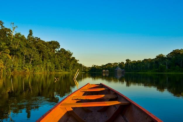 Barco de madeira no meio de um lago de águas azuis, a água é calma e reflete o céu e as montanhas