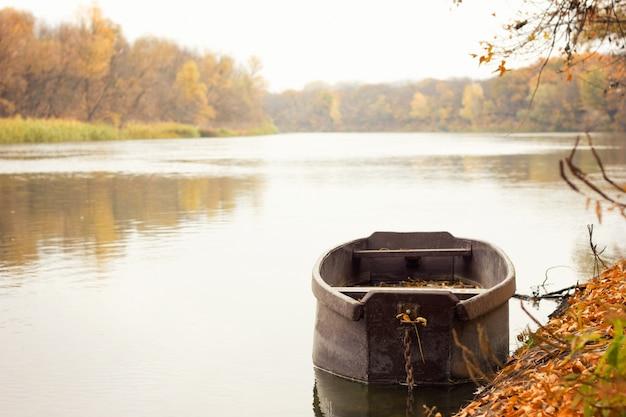 Barco de madeira no rio, paisagem de outono, com um lugar sob a inscrição