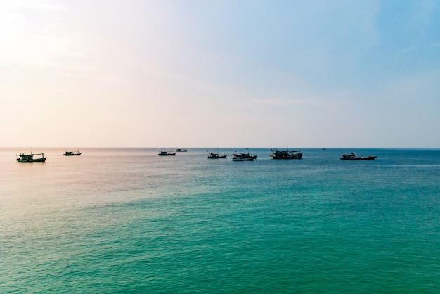 Barco de madeira tradicional no camboja. foto de paisagem do mar ao nascer do sol. vista mar e céu com a silhueta do barco. litoral da ilha de koh rong. cartão de férias no sul da ásia.
