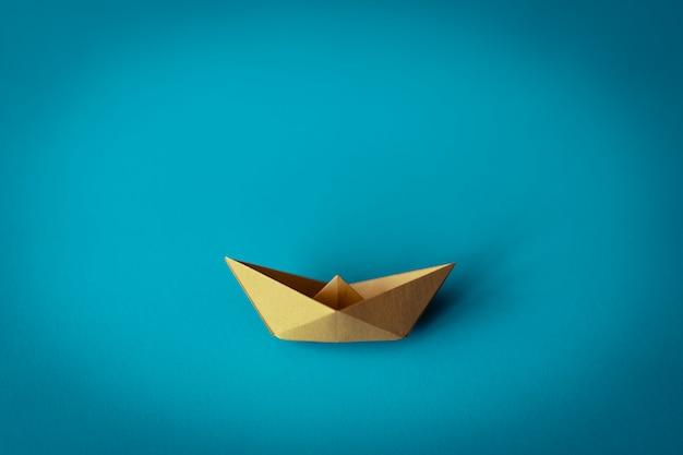 Barco de papel amarelo sobre fundo azul, com espaço de cópia, aprendizagem e conceito de educação