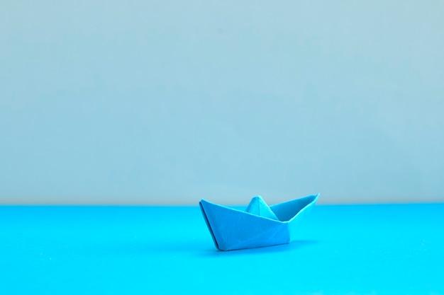 Barco de papel azul sobre fundo ciano. conceito de liderança, gestão, negócios, motivação