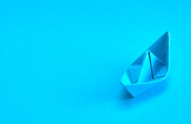 Barco de papel azul sobre fundo ciano. conceito de liderança,