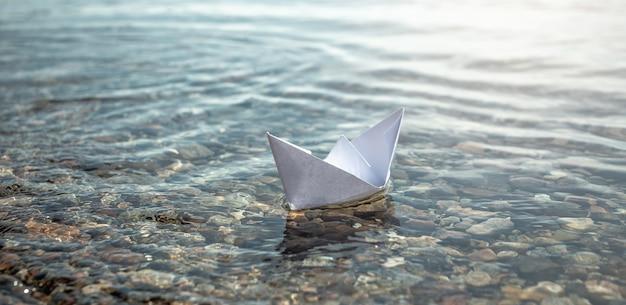 Barco de papel branco nas águas claras de um grande lago com fundo pedregoso.