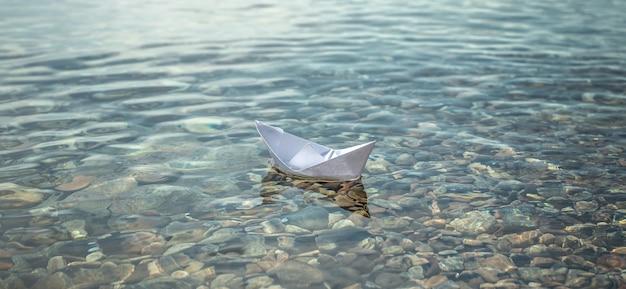 Barco de papel branco nas águas claras de um lago com fundo pedregoso.