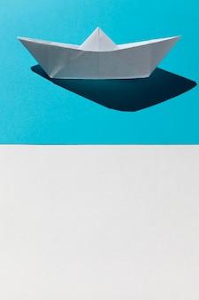 Barco de papel branco sobre fundo azul