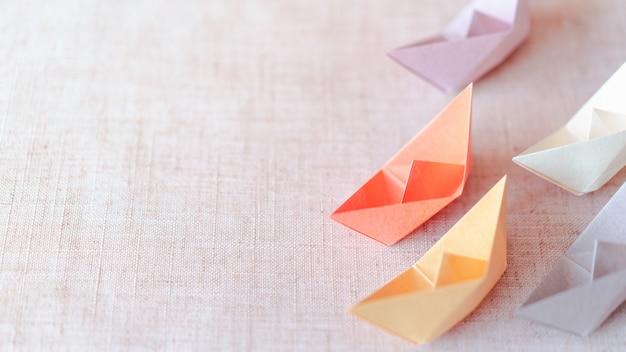 Barco de papel de cor pastel sobre fundo de textura de lona com espaço de cópia