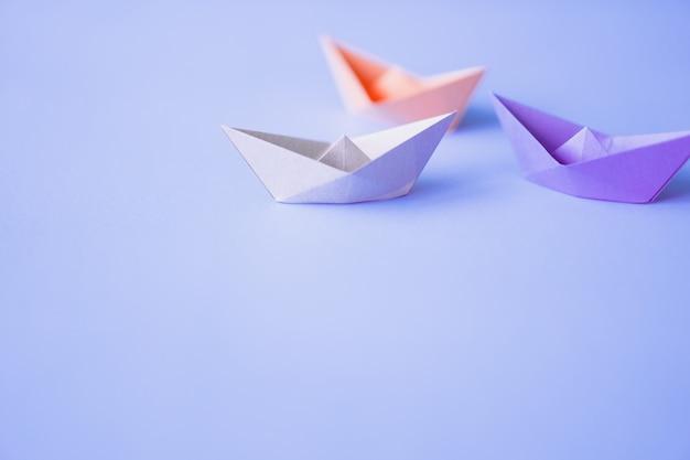 Barco de papel de cor pastel sobre fundo limpo, com espaço de cópia