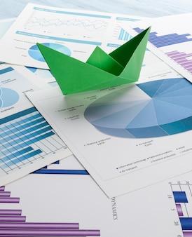 Barco de papel em gráficos de negócios
