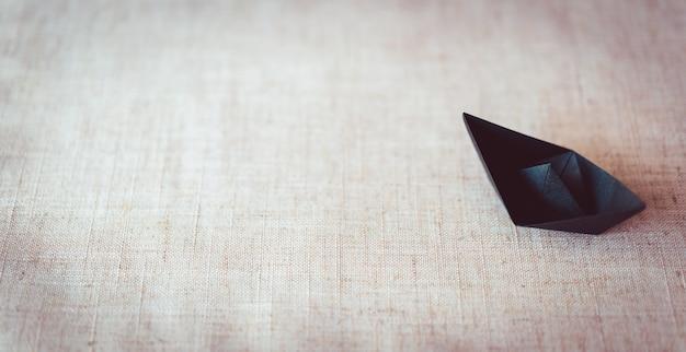 Barco de papel preto sobre fundo de textura de lona com espaço de cópia