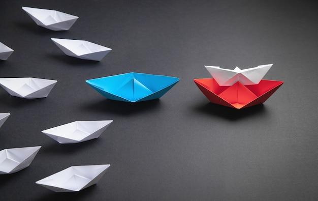 Barco de papel vermelho, azul e branco. conceito de liderança