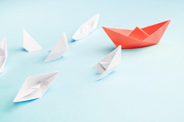 Barco de papel vermelho e muitos navios afundando