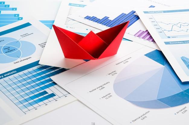Barco de papel vermelho em gráficos de negócios azuis