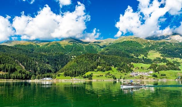 Barco de passageiros em reschensee, um lago artificial no tirol do sul, nos alpes italianos
